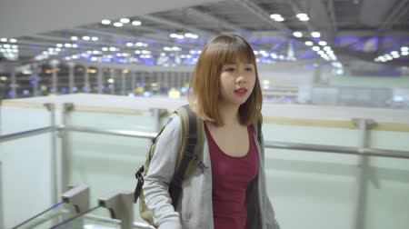 сумки : Young Asian backpacker woman tourist walking in terminal hall while going to boarding flight at the departure gate in international airport. Lifestyle backpack tourist travel holiday concept.