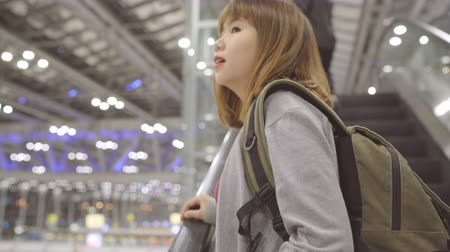 backpacken : Young Asian backpacker woman tourist walking in terminal hall while going to boarding flight at the departure gate in international airport. Lifestyle backpack tourist travel holiday concept.