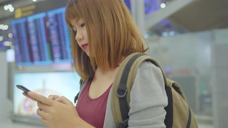 backpacken : Happy Asian woman using and checking her smartphone in terminal hall while waiting her flight at the departure gate in international airport. Women happy in airport concept.