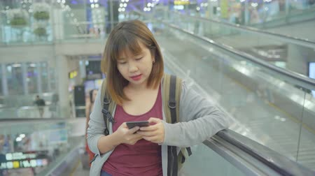 bavul : Happy Asian woman using and checking her smartphone in terminal hall while waiting her flight at the departure gate in international airport. Women happy in airport concept.