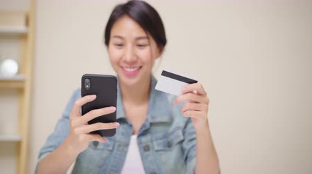 ispanico : Beautiful Asian woman using smartphone buying online shopping by credit card while wear casual sitting on desk in living room at home. Lifestyle women working at home concept.