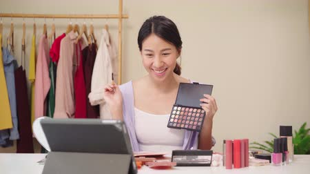 öz : Beauty blogger present beauty cosmetics sitting in front tablet for recording video. Happy beautiful young Asian woman use cosmetics review make up tutorial broadcast live video to social network.