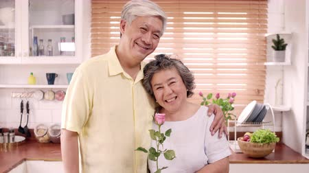 dişlek : Asian elderly couple feeling happy smiling and holding flower and looking to camera while relax in kitchen at home. Lifestyle Senior family enjoy time at home concept. Portrait looking at camera. Stok Video