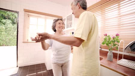 nagymama : Asian elderly couple dancing together while listen to music in kitchen at home, sweet couple enjoy love moment while having fun when relaxed at home. Lifestyle senior family relax at home concept. Stock mozgókép