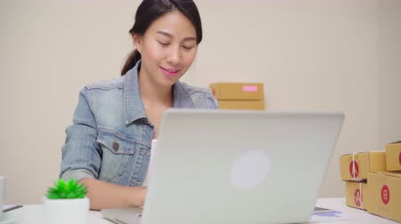 inventario : Beautiful smart Asian young entrepreneur business woman owner of SME online checking product on stock and save to computer working at home. Small business owner at home office concept.