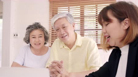 dokumentum : Asia smart female agent offers health insurance for elderly couples by document, tablet and laptop. Aged Asian couple consulting with insurance agent while sitting together with at home.