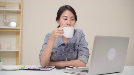 residencial : Beautiful young smiling asian woman working on laptop and drinking coffee in living room at home. Asia business woman working document finance and calculator in her home office. Enjoying time at home.
