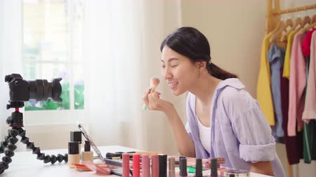 miroir : Beauty blogger present beauty cosmetics sitting in front camera for recording video. Happy beautiful young Asian woman use cosmetics review make up tutorial broadcast live video to social network.