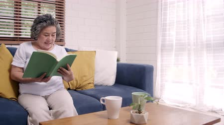 lezing : Asian elderly woman reading a book in living room at home. Chinese female lying on sofa when relaxed at home. Enjoying time lifestyle senior woman at home concept.