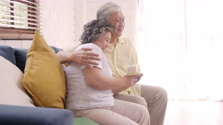 abraços : Asian elderly couple man holding cake celebrating wifes birthday in living room at home. Japanese couple enjoy love moment together at home. Lifestyle senior family at home concept.