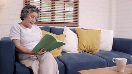 descontraído : Asian elderly woman reading a book in living room at home. Chinese female lying on sofa when relaxed at home. Enjoying time lifestyle senior woman at home concept.
