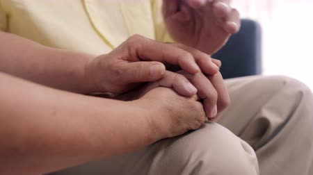 together trust : Asian elderly couple holding their hands while taking together in living room, couple feeling happy share and support each other lying on sofa at home. Lifestyle Senior family at home concept.