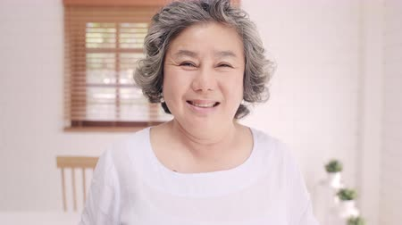 dişlek : Asian elderly woman feeling happy smiling and looking to camera while relax on the sofa in living room at home. Lifestyle senior women at home concept. Stok Video