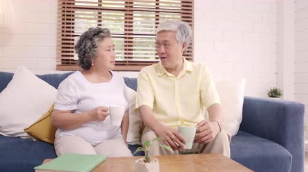 çay : Asian elderly couple drinking warm coffee and talking together in living room at home, couple enjoy love moment while lying on sofa when relaxed at home. Lifestyle senior family at home concept.