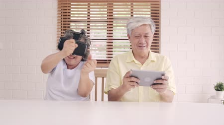 konzol : Asian elderly couple using tablet and virtual reality simulator playing games in living room, couple feeling happy using time together lying on table at home. Lifestyle Senior family at home concept. Stock mozgókép
