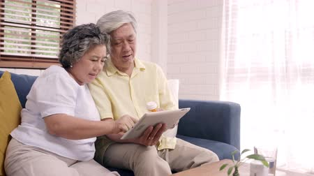 таблетки : Asian elderly couple using tablet search medicine information in living room, couple using time together while lying on sofa when relaxed at home. Senior family health at home concept.