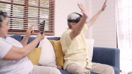 konzol : Asian elderly couple using tablet and virtual reality simulator playing games in living room, couple feeling happy using time together lying on sofa at home. Lifestyle Senior family at home concept.