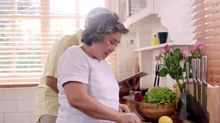 eat : Asian elderly couple cut tomatoes prepare ingredient for making food in the kitchen, Couple use organic vegetable for healthy food at home. Lifestyle senior family making food at home concept. Stock Footage