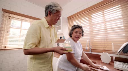 abraços : Asian elderly couple man holding cake celebrating wifes birthday in kitchen at home. Chinese couple enjoy love moment together at home. Lifestyle senior family at home concept. Vídeos