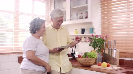 выбирать : Asian elderly couple using tablet prepare ingredient for making food in the kitchen, Couple use organic vegetable for healthy food at home. Lifestyle senior family making food at home concept.