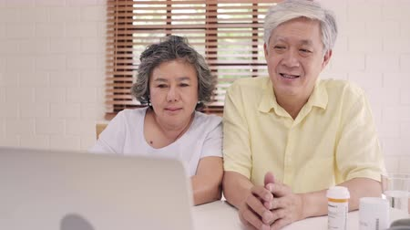 conference table : Asian elderly couple using laptop conference with doctor about medicine information in living room, couple using time together while lying on sofa at home. Senior family health at home concept.