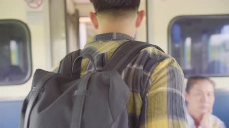 ingázik : Traveler Asian man walking and looking for seat while taking a train, Young male tourist backpacker journey in Thailand. Lifestyle teen men travel concept. Stock mozgókép