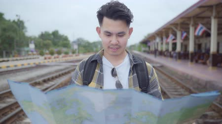 lezing : Traveler Asian man direction and looking on location map while spending holiday trip and waiting train at train station, Young male tourist backpacker enjoy journey. Lifestyle men travel concept.