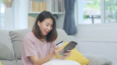 электронная коммерция : Young smiling Asian woman using tablet buying online shopping by credit card while lying on sofa when relax in living room at home. Lifestyle latin and hispanic ethnicity women at house concept.