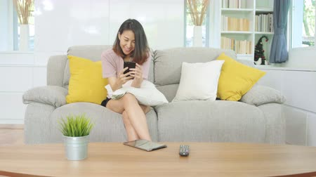 ispanico : Young Asian woman using smartphone checking social media feeling happy smiling while lying on the sofa when relax in living room at home. Lifestyle latin and hispanic ethnicity women at house concept.
