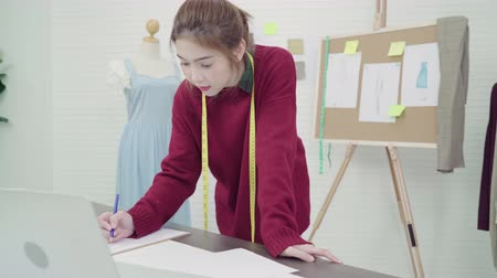 têxteis : Professional beautiful Asian female fashion designer working with fabric sketches and using laptop find drawing clothing design at the studio. Lifestyle women working concept. Stock Footage