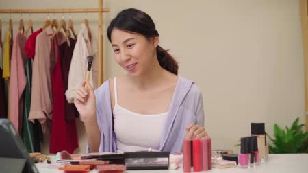 revisão : Slow motion - Beauty blogger present beauty cosmetics sitting in front camera for recording video. Happy beautiful young Asian woman use cosmetics review make up tutorial broadcast live video.