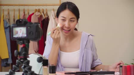 miroir : Slow motion - Beauty blogger present beauty cosmetics sitting in front camera for recording video. Happy beautiful young Asian woman use cosmetics review make up tutorial broadcast live video.