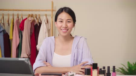 miroir : Beauty blogger present beauty cosmetics sitting in front tablet for recording video. Happy beautiful young Asian woman use cosmetics review make up tutorial broadcast live video to social network.