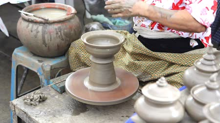 kamenina : Close up of hands making earthen jar on a wheel in traditional Thailand style