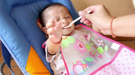 infant formula : Cute asian baby happy and smile on mother feeding with spoon