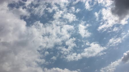 evaporate : White clouds disappear in the hot sun on blue sky.Time-lapse motion clouds blue sky background.Clouds running across the blue sky.Timelapse cloudscape. Cumulus clouds form against a brilliant blue sky.