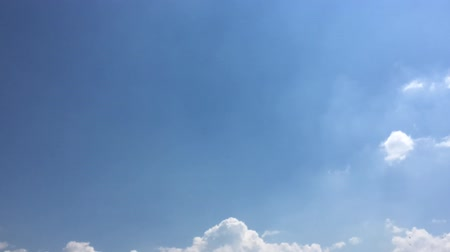 midair : White clouds disappear in the hot sun on blue sky. Loop features time lapse motion clouds backed by a beautiful blue sky. Time-lapse motion clouds blue sky background and sun. Stock Footage