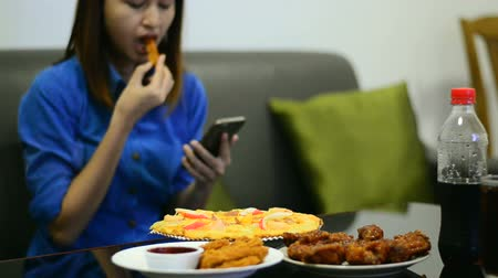 sofá : Asian girl eating snack and chicken in pizza set while use smartphone.