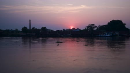 Sunset over village beside river Chao Phraya, Thailand