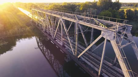 закат : A high-speed train drives a bridge across the river at sunset Стоковые видеозаписи