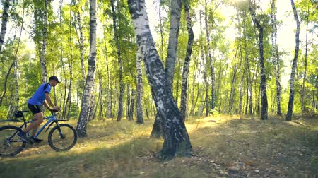 ailelerin : Young man biking on a forest road in a sammer day