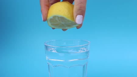 vitamina : Female hand squeezes lemon juice into glass of water on a blue background. Stock Footage