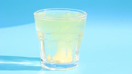 dose de : Effervescent tablet in a glass with water on blue background.