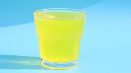 vitamina : Yellow effervescent tablet with vitamin C in glass on a blue background.
