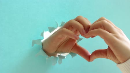 happiness symbol : Female hands in the shape of a heart on torn blue paper background. Stock Footage