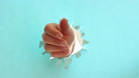 kciuk : Female hand raises thumb up on torn blue paper background. Wideo