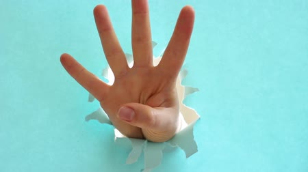 čtvrtý : Female hand makes a countdown on background of blue torn paper.