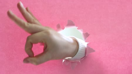 szakadt : Female hand shows OK sign on pink paper background.