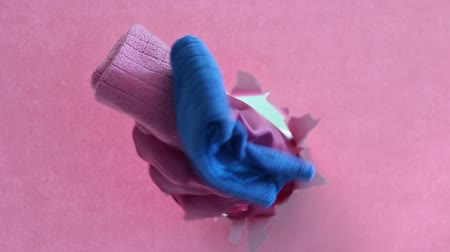 szakadt : Female hand in a pink glove holds a rags on background of torn paper Stock mozgókép