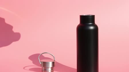 reutilizável : Black reusable bottle for water on a pink background Stock Footage